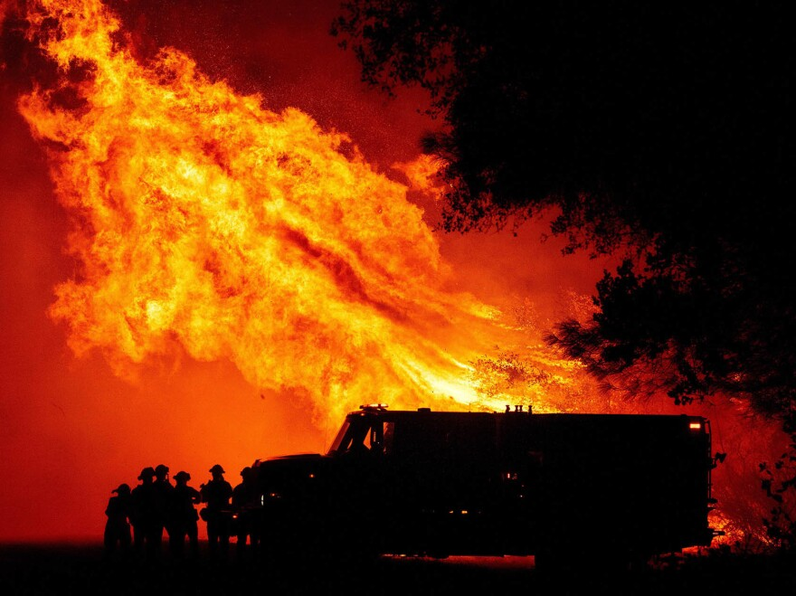 Communities have struggled to find funding to clear brush and make neighborhoods more safe from fires. Here, firefighters watch as flames tower over their truck in Oroville, Calif.