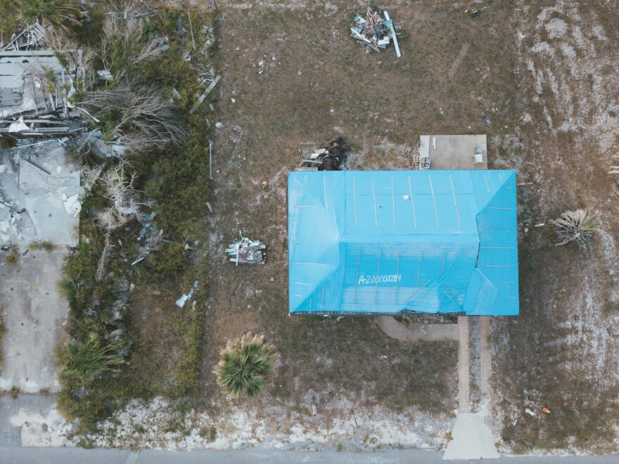 A photo from above showing a home with a blue tarp on its roof and a number written in large white letters. Next to the house is a pile of brush and rubble