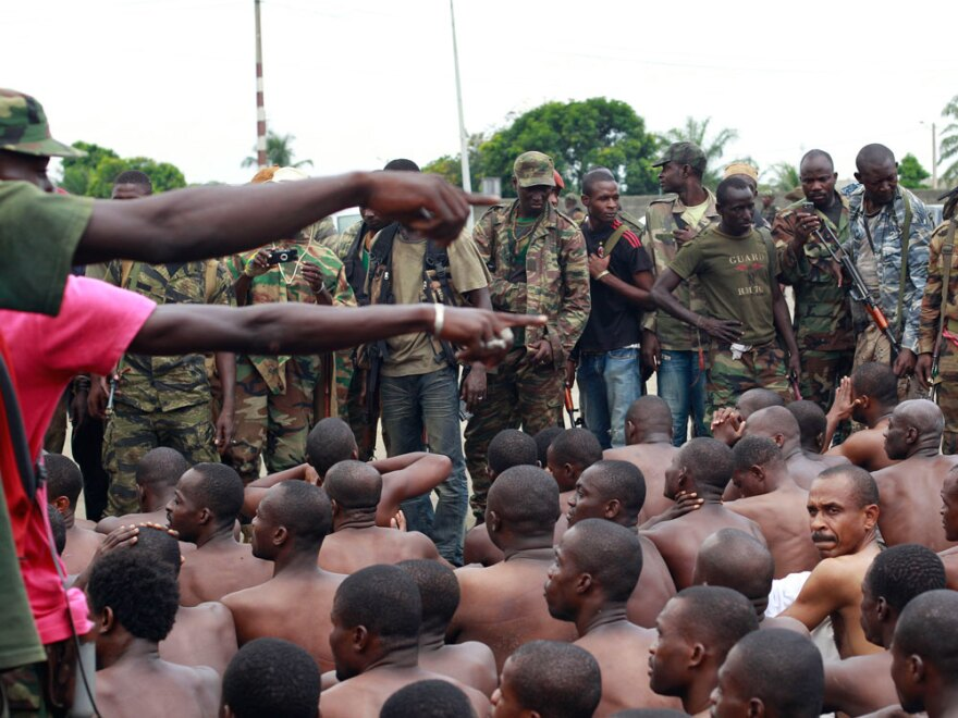 Soldiers loyal to Alassane Ouattara point to men they claim to recognize among several dozen prisoners captured.