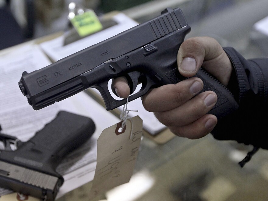 At a gun shop in Phoenix, a  customer holds a handgun. Among the executive actions President Obama is expected to propose is an expansion of background checks for gun buyers.