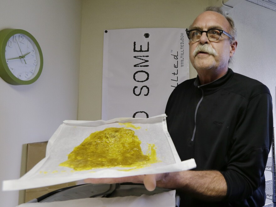 Jim Andersen displays butane hash oil at a marijuana growing facility in Seattle in April 2013. The state's licensed producers will be required to use professional-grade equipment when making the extracts.