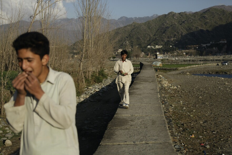 Youths walk on a wall that separates the Swat River from the nearby village of of Imam Dherai, once the headquarters of Taliban rule in the Swat Valley.