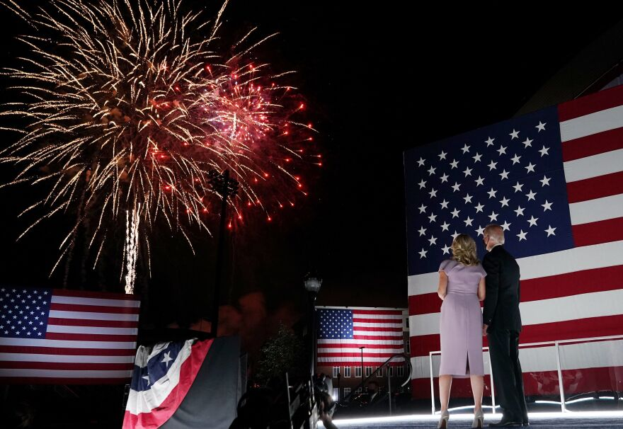 Jill and Joe Biden, wearing face masks, watch fireworks outside the Chase Center in Wilmington, Del., after Biden's acceptance speech for the Democratic presidential nomination.