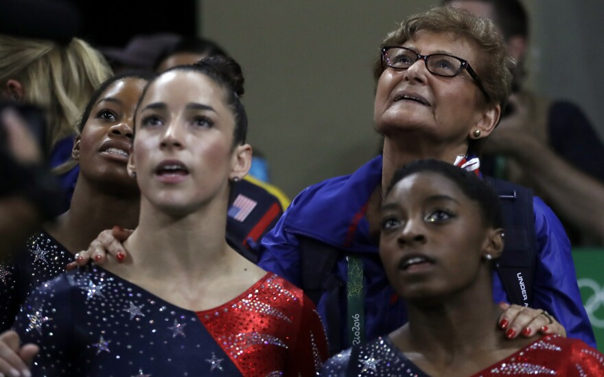 Marta Karolyi, the national team coordinator for USA Gymnastics, looks at the scoreboard along with (from right) Simone Biles, Aly Raisman and Gabby Douglas during the women's qualification on Sunday. Karolyi, 73, is widely credited with helping make the U.S. women the best in the world. She is stepping down after the Rio Games.