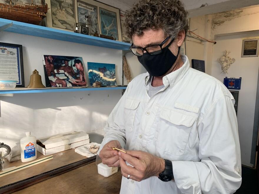 archaeologist corey malcom holds the whistle from the Santa margarita, a spanish treasure ship
