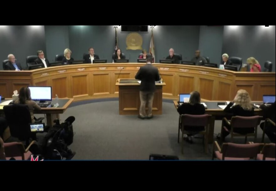 man with back to camera speaks to commissioners on a panel