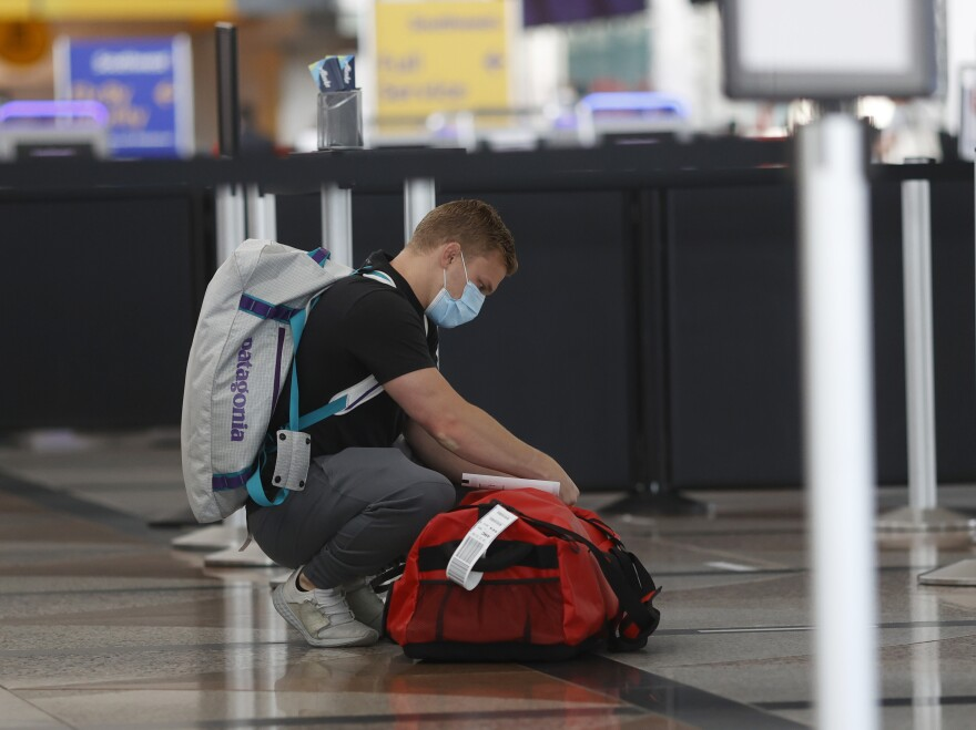 A passenger wears a face covering at Denver International Airport as he checks his bags.