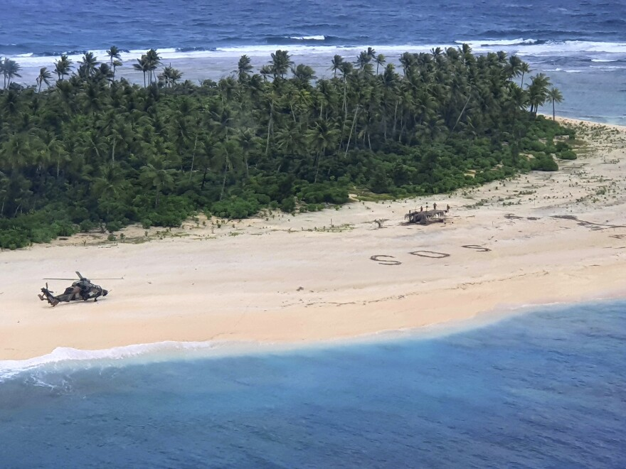 In this photo provided by the Australian Defence Force, an Australian Army helicopter lands on Pikelot Island in the Federated States of Micronesia to rescue three stranded mariners who had been missing for nearly three days.