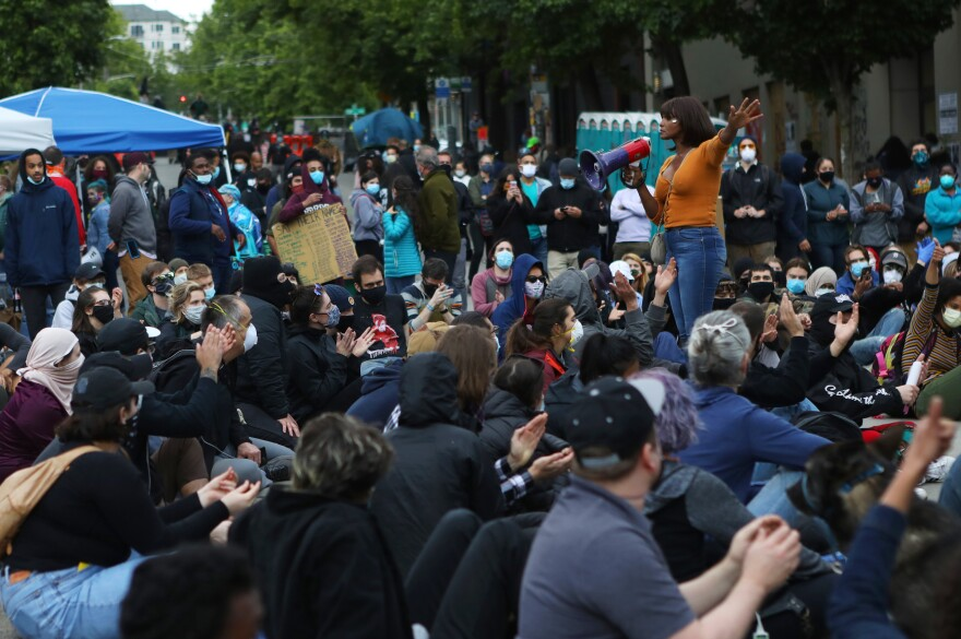 Protesters listen to a speaker in the occupied zone. Activists said it's too early to relinquish the space. Only a few demands have been met — a ban on police chokeholds, for example — and talks are still going on for the bigger asks, namely slashing the Seattle Police Department's budget and redirecting funds to health and social services.