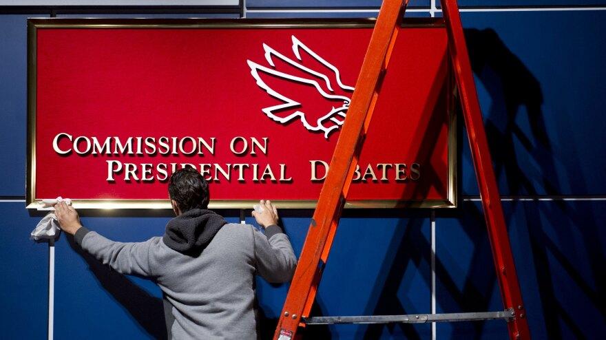 A worker cleans a sign before Tuesday's presidential debate at Hofstra University in Hempstead, N.Y.