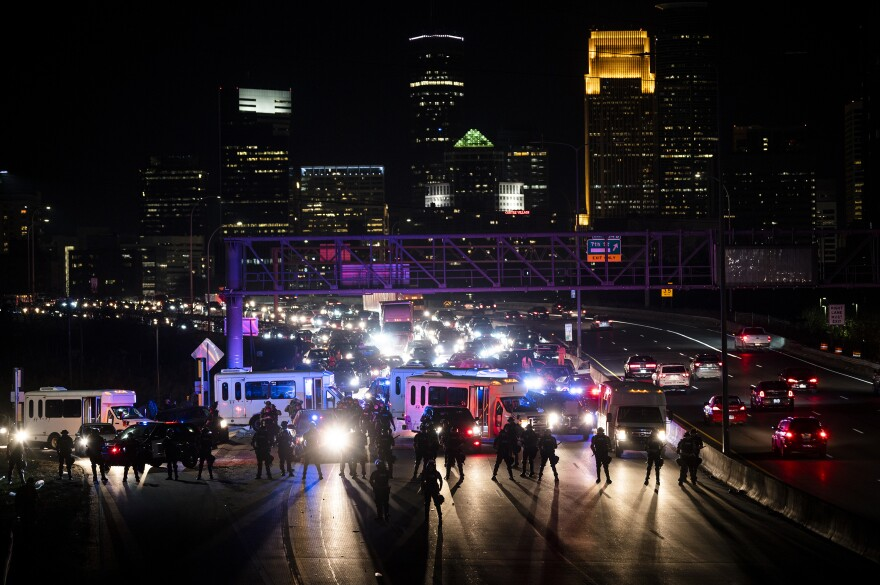 Police block traffic as demonstrators march on to highway I-94 on Wednesday in Minneapolis, Minn.