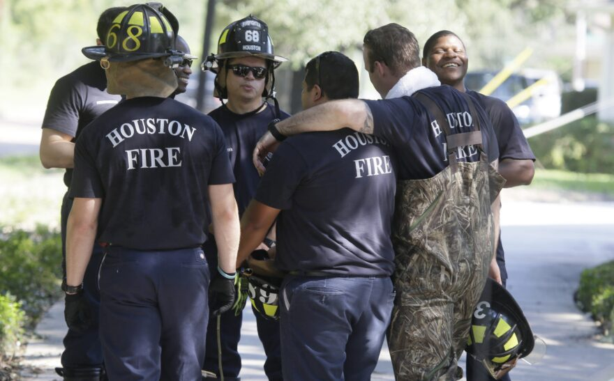 Houston firefighters gather during a door-to-door survey of a neighborhood that was hit by floodwaters from Tropical Storm Harvey in Houston on Thursday, Aug. 31, 2017. (LM Otero/AP)