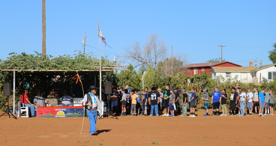 Photo of a man wearing jeans and a decorated vest stands in the middle of a corral with red dirt holding a flag. A group of young boys stands behind him.