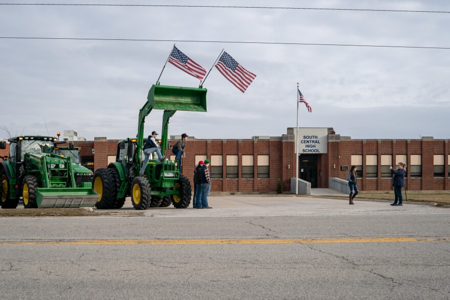 Parents and staff take pictures of students and their tractors at South Central High School's  Drive Your Tractor To School Day.
