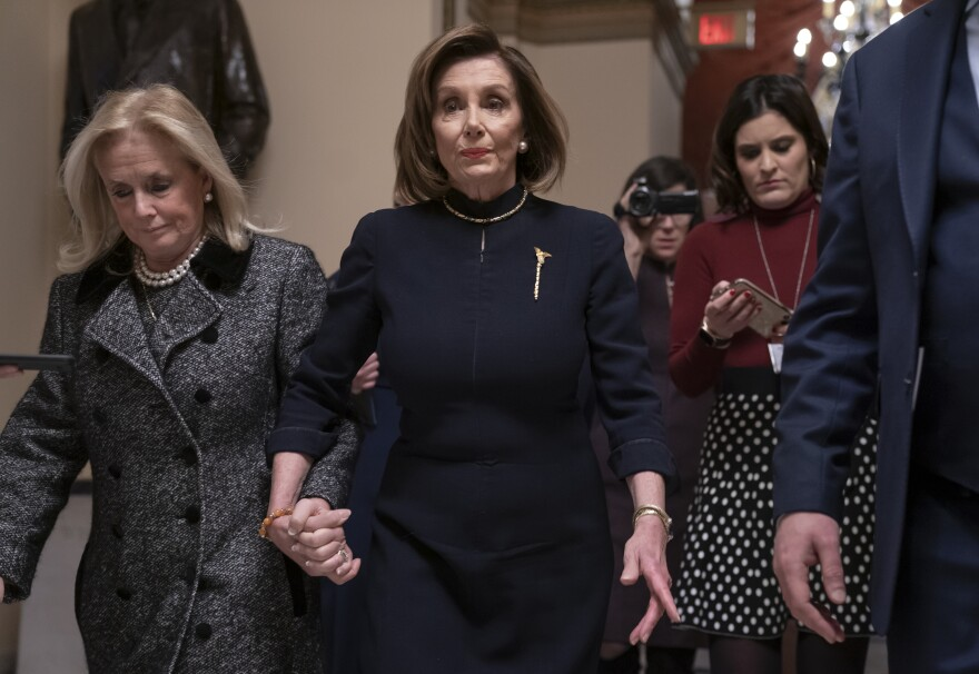 House Speaker Nancy Pelosi, D-Calif., holds hands with Rep. Debbie Dingell, D-Mich., as they walk to the chamber where the House begins debate on the impeachment charges against President Trump.