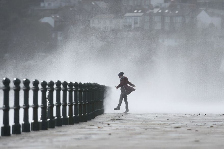 A woman stands as waves crash against the sea wall at Penzance, southwestern England, as the remnants of Ophelia begin to hit parts of the U.K. and Ireland.
