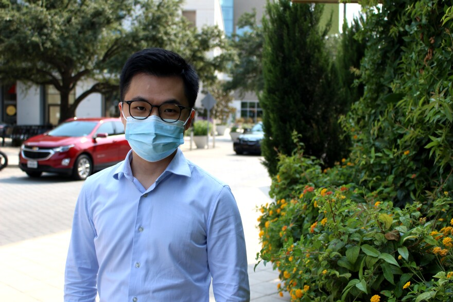 Kevin Wang wears a mask as he stands in front of the road.