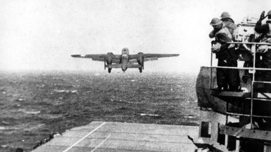 U.S. Navy crewmen watch a B-25 bomber take off from the USS Hornet for the Doolittle Raid on Tokyo on April 18, 1942.