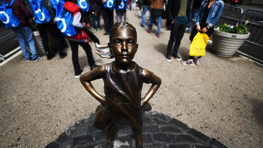 The <em>Fearless Girl</em> statue stands facing <em>Charging Bull</em> as tourists take pictures in New York on April 12, 2017.