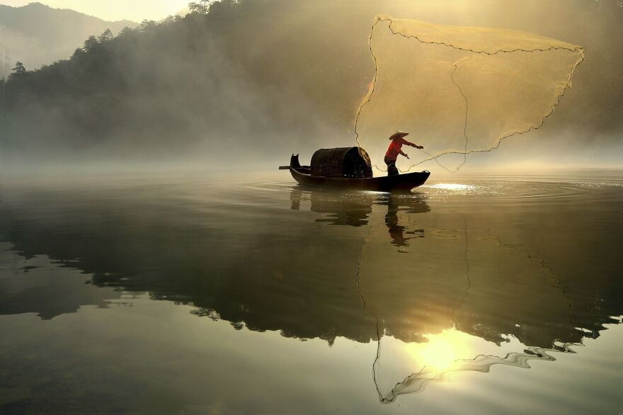 A fisherman throws out his net in the hazy morning light.