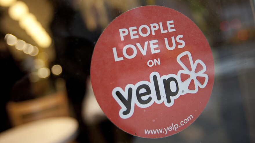 The Yelp Inc. logo is displayed in the window of a restaurant in New York in 2012.