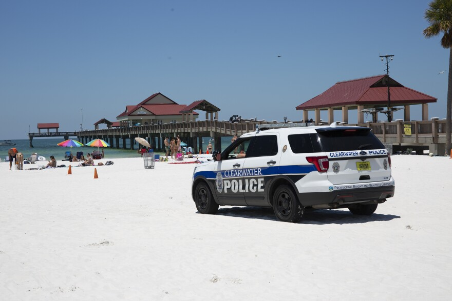 A police SUV sits on the sand.