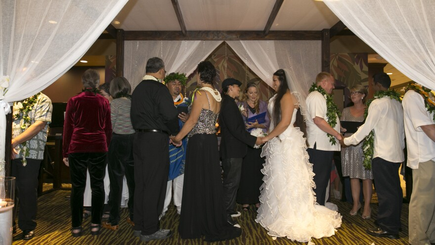 Several same-sex couples hold a group wedding ceremony Monday at the Sheraton Waikiki in Honolulu.