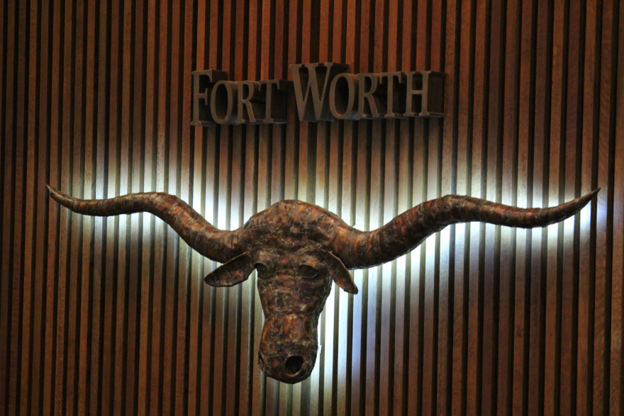 In this photo, a sculpture of a longhorn steer hangs on a wall, backlit, below the words Fort Worth in the Fort Worth City Council chambers.