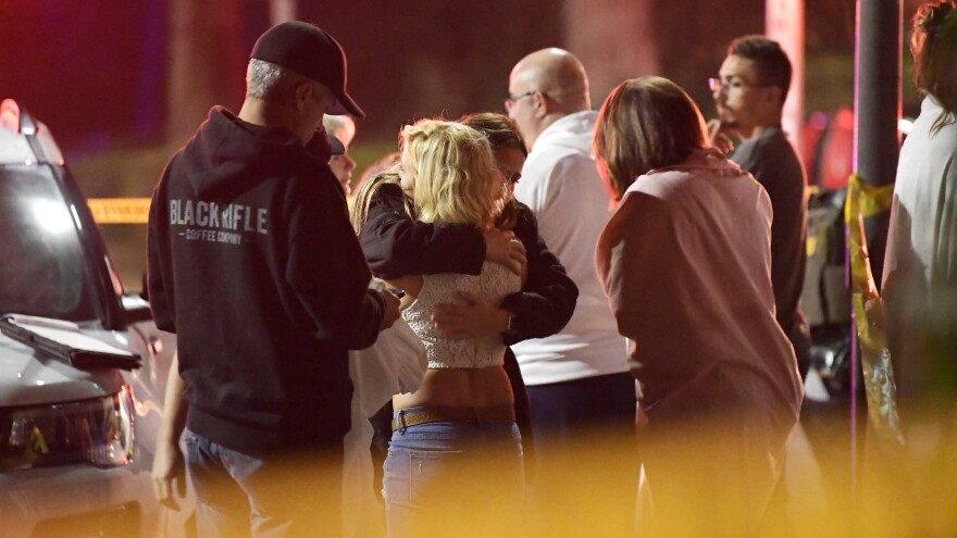 People comfort each other outside the Borderline Bar & Grill in Thousand Oaks, Calif., where a gunman opened fire and killed 12 people.