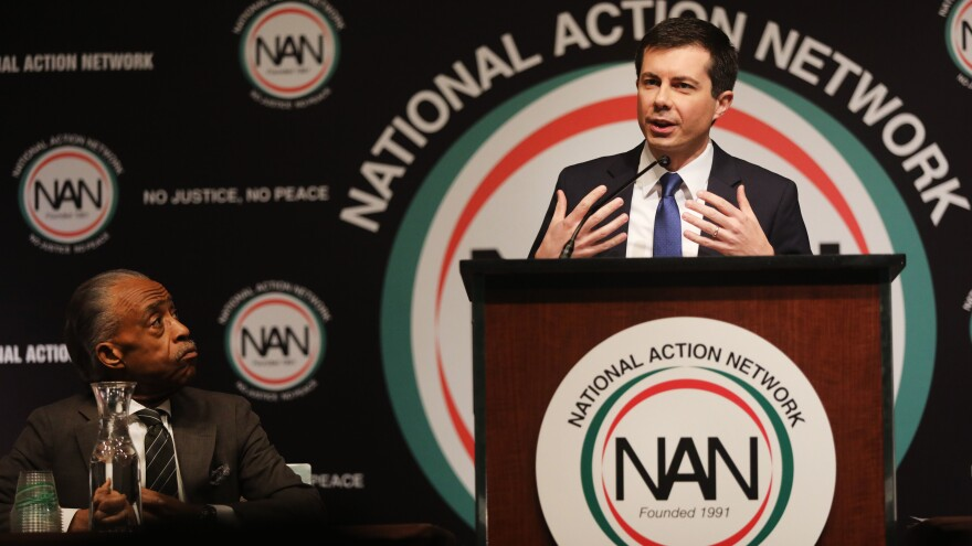 With the Rev. Al Sharpton looking on, Democratic presidential hopeful South Bend, Ind., Mayor Pete Buttigieg speaks at the National Action Network's annual convention Friday in New York City.