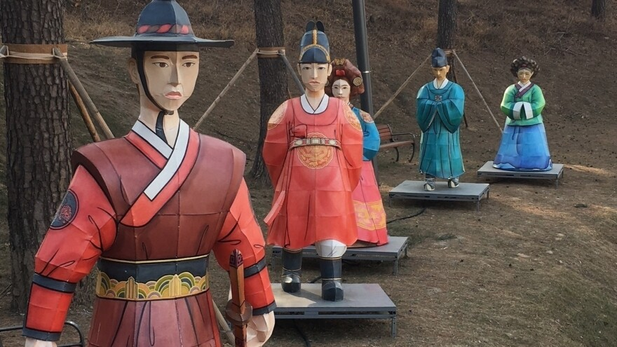 """Figures in traditional dress line a hillside across the street from the Olympic Park in """"sub-host"""" city Gangneung."""