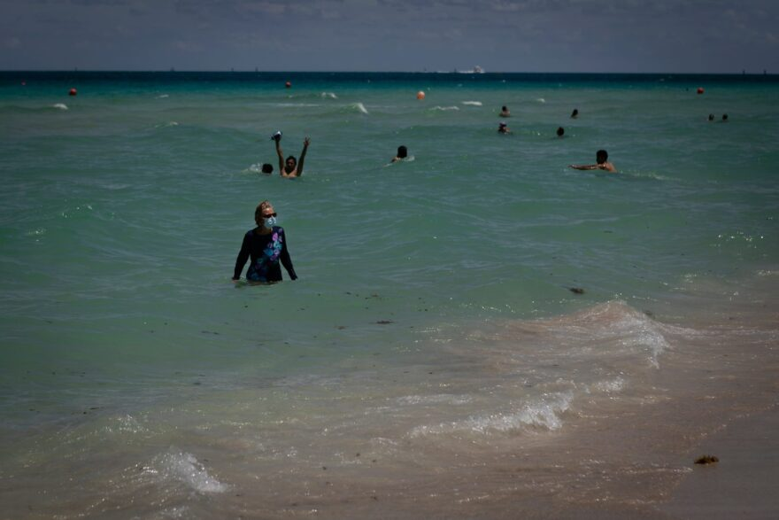 Swimmers enjoy the water in Miami Beach. Florida is reporting record daily totals of new coronavirus cases.