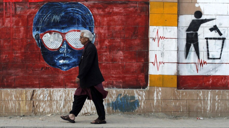 A man walks past one of the many graffiti-covered walls in Karachi, Pakistan, on Dec. 27, 2013. Provincial lawmakers have voted to ban graffiti, but few expect the measure to be enforced.