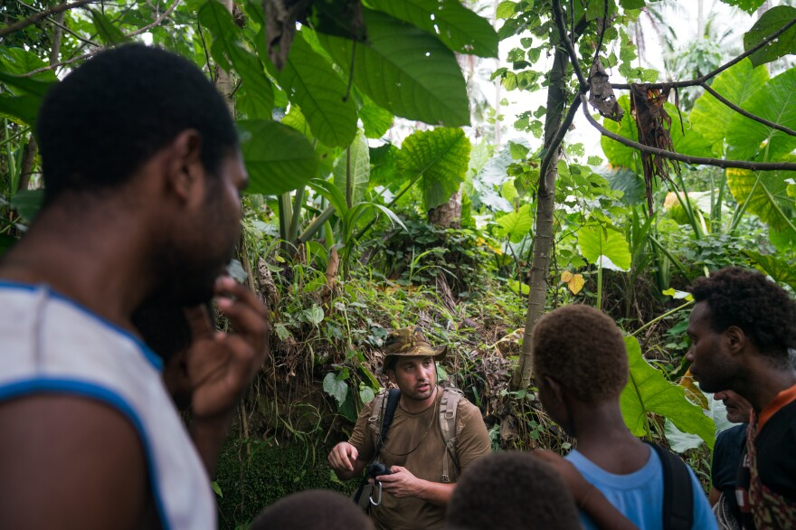U.S. researcher Justin Taylan talks with residents who lead him to see World War II wreckage on a coconut plantation.