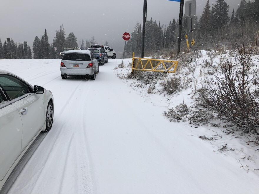 Photo of cars lined up on a snowy road.