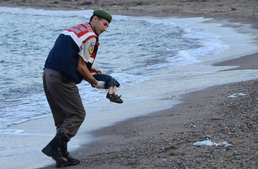 A Turkish paramilitary police officer carries the body of 2-year-old Syrian refugee Alan Kurdi, found washed ashore near the Turkish resort of Bodrum in September 2015.