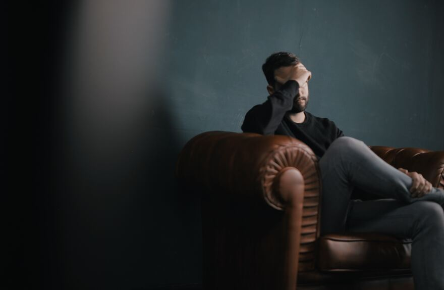 man sits on plush sofa. His hand is covering his face.