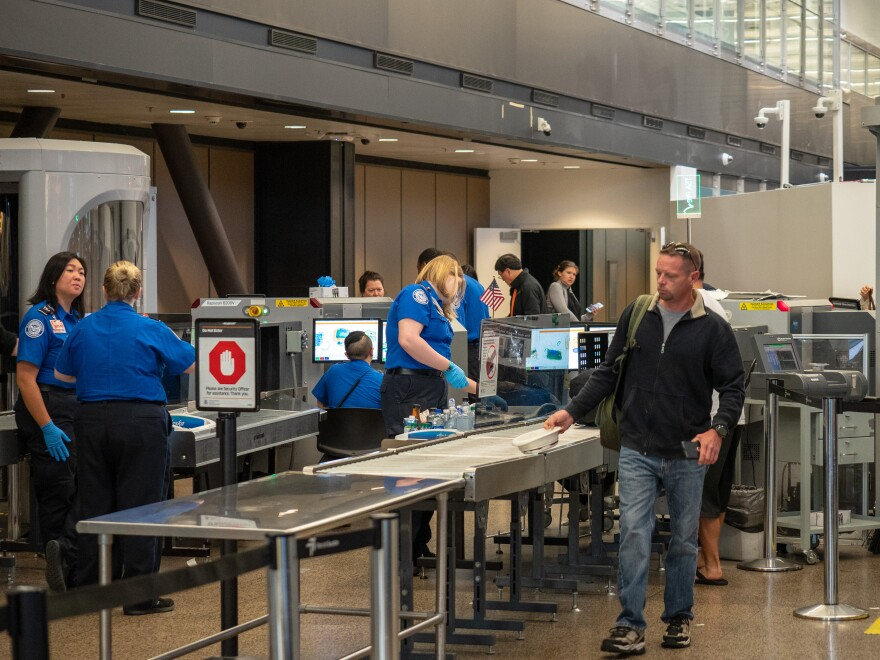 Picture of a man walking through an airport security screening station.
