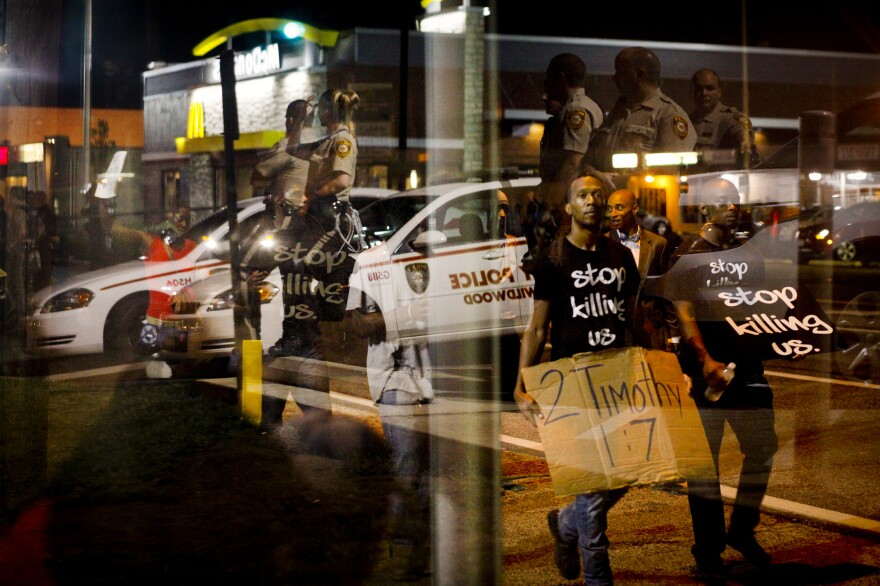 Law enforcement officers are reflected in a window as demonstrators walk past a bus stop in Ferguson.