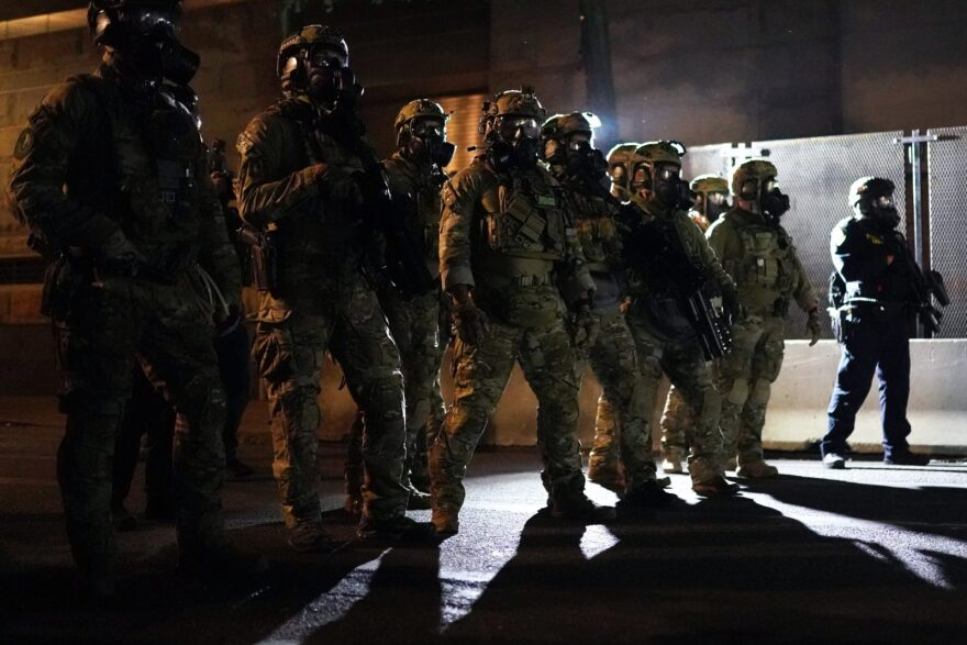 Federal officers form a police line in front of the Mark O. Hatfield U.S. Courthouse in the early hours in Portland, Oregon.