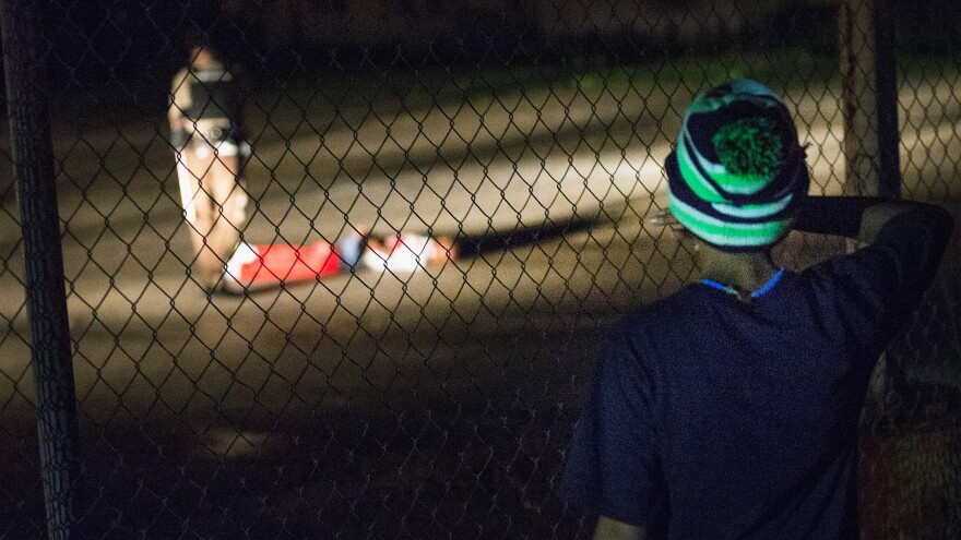 A young boy looks at a man in police custody who apparently suffered gunshot wounds Sunday night in Ferguson, Mo.