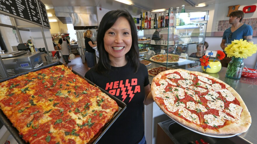 "Ann Kim, owner of Hello Pizza in Edina, Minn., holds a Sicilian pan pie and a Hello Rita pizza. ""Women can make progress in pizza that is harder in the macho restaurant world,"" Kim says."