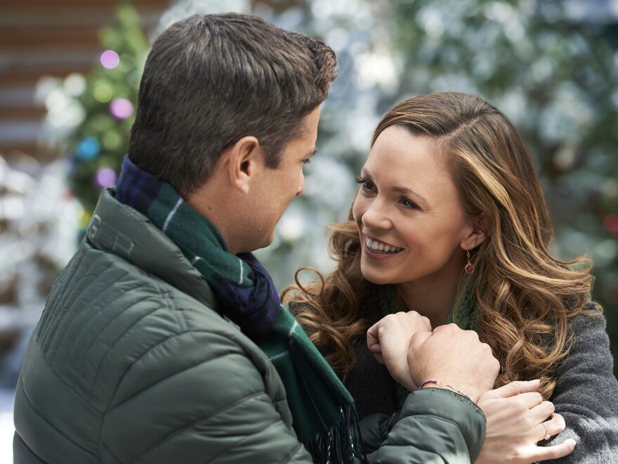 Wes Brown and Rachel Boston canoodle in <em>Check Inn To Christmas</em>.