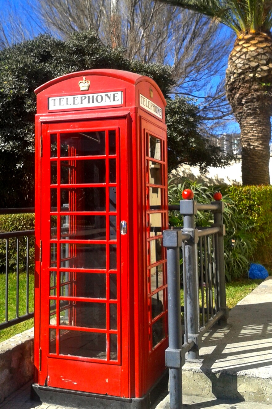 A quintessentially British phone booth greets those arriving on the British side of the border with Spain. Nearby is a palm tree — a reminder that this is not in the British Isles.