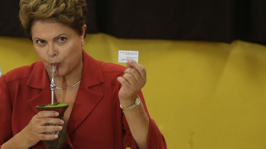 Brazil's President Dilma Rousseff sips a drink while showing her voting receipt at a polling center in Porto Alegre Sunday. The incumbent faces a run-off challenge from Aecio Neves.