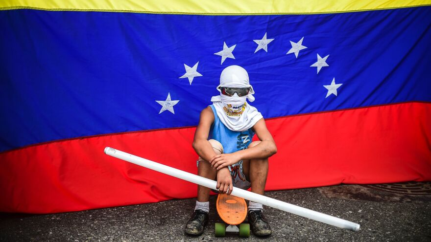 An opposition activist sits in front of a Venezuelan flag during a protest against the constituent assembly in Caracas last week. Opponents of President Nicolas Maduro have struggled to find a foothold in their struggle against his consolidation of power.