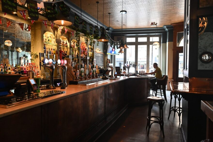 A single customer sits at the bar in a near-empty pub in central London on after the UK government announced stringent social distancing advice including avoiding pubs and restaurants as a measure to kerb the spread of novel coronavirus COVID-19.