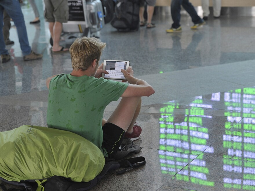 The departure board is reflected on the floor as a passenger sits in the international terminal at Ngurah Rai Airport on the Indonesian resort island of Bali on Friday. Indonesian authorities closed five airports after the eruption of a volcano on Java.
