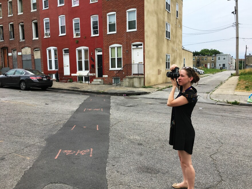 Baltimore-based artist Amy Berbert photographs a scene where someone was killed one year ago, as part of her series <em>Stains on the Sidewalk.</em>