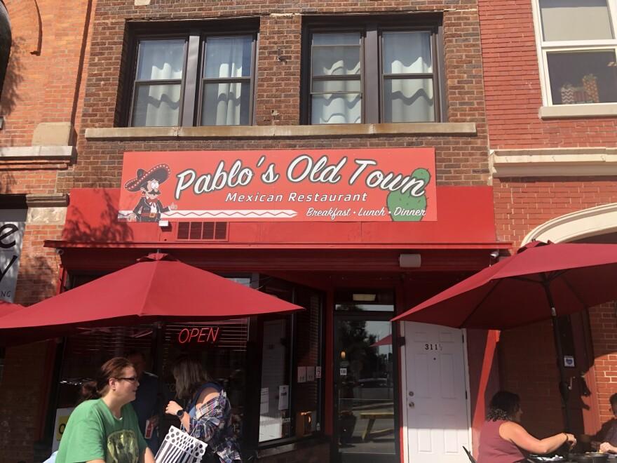 Fuera del restaurante Pablo Old Town.  El nombre del restaurante está impreso en un gran cartel de metal.  Hay dos mesas con sombrillas rojas afuera.  Varios clientes se sientan en cada uno de ellos.